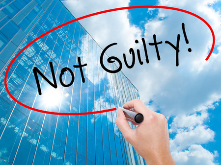 Man Hand writing NOT GUILTY with black marker on visual screen. Business, technology, internet concept. Modern business skyscrapers background. Stock Image Stock Photo
