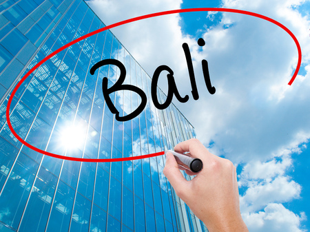 Man Hand writing Bali  with black marker on visual screen. Business, technology, internet concept. Modern business skyscrapers background. Stock Photo Stock Photo