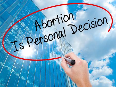 poronienie: Człowiek Ręczne pisanie aborcja jest osobista decyzja z czarnym markerem na ekranie wizualnej. Biznes, technologia, internet koncepcji. Nowoczesne wieżowce biznesu w tle. Zdjęcie Seryjne Zdjęcie Seryjne