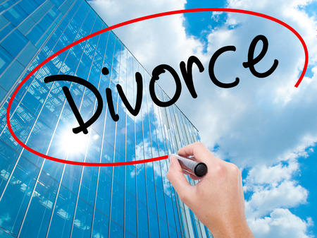 Man Hand writing Divorce  with black marker on visual screen. Business, technology, internet concept. Modern business skyscrapers background. Stock Photo Stock Photo