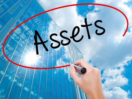 Man Hand writing Assets with black marker on visual screen. Business, technology, internet concept. Modern business skyscrapers background. Stock Photo Stock Photo