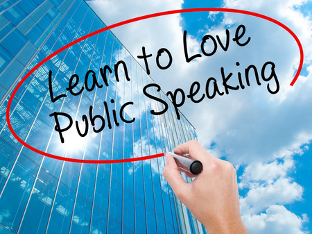 debating: Man Hand writing Learn to Love Public Speaking with black marker on visual screen. Business, technology, internet concept. Modern business skyscrapers background. Stock Image