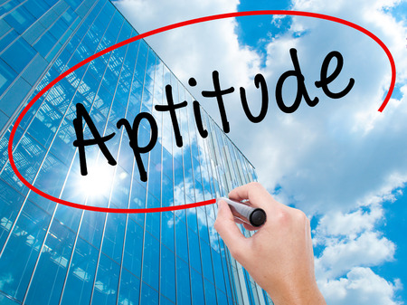 aptitude: Man Hand writing Aptitude with black marker on visual screen.  Business, technology, internet concept. Modern business skyscrapers background. Stock Photo