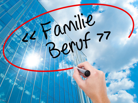 Man Hand writing familie beruf (Family Occupation in German) with black marker on visual screen.  Business, technology, internet concept. Modern business skyscrapers background. Stock Photo
