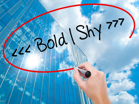 outspoken: Man Hand writing Bold - Shy  with black marker on visual screen.  Business, technology, internet concept. Modern business skyscrapers background. Stock Photo