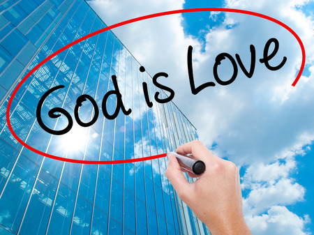 Man Hand writing God is Love with black marker on visual screen. Business, technology, internet concept. Modern business skyscrapers background. Stock Photo