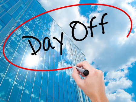 Man Hand writing Day Off  with black marker on visual screen.  Business, technology, internet concept. Modern business skyscrapers background. Stock Photo