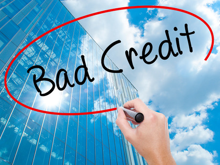 Man Hand writing Bad Credit with black marker on visual screen. Business, technology, internet concept. Modern business skyscrapers background. Stock Photo