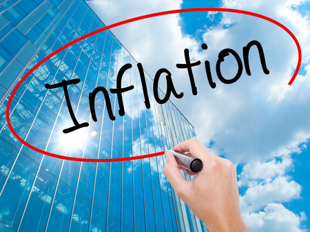 economic theory: Man Hand writing Inflation with black marker on visual screen.  Business, technology, internet concept. Modern business skyscrapers background. Stock Photo Stock Photo