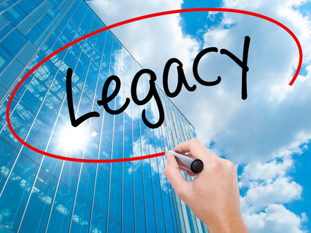 Man Hand writing Legacy with black marker on visual screen.  Business, technology, internet concept. Modern business skyscrapers background. Stock Photo Stock Photo