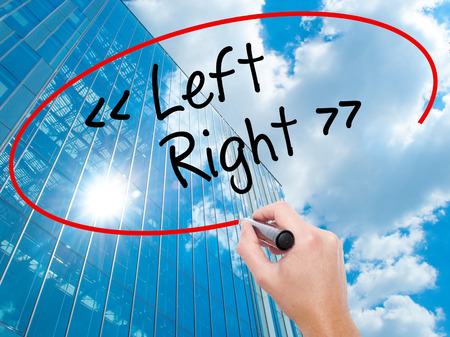 Man Hand writing Left - Right with black marker on visual screen.  Business, technology, internet concept. Modern business skyscrapers background. Stock Photo