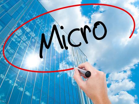 Man Hand writing Micro with black marker on visual screen.  Business, technology, internet concept. Modern business skyscrapers background. Stock Photo