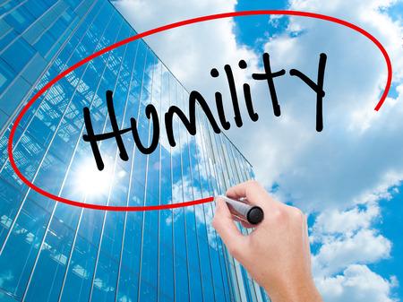 soltería: Hombre de la mano escribiendo Humildad con marcador negro en la pantalla visual. Negocios, la tecnología, el concepto de internet. Fondo moderno de los rascacielos de negocios. Foto de stock