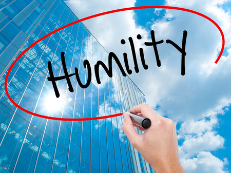 Man Hand writing Humility  with black marker on visual screen.  Business, technology, internet concept. Modern business skyscrapers background. Stock Photo Stock Photo