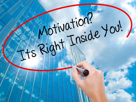 Man Hand writing Motivation? Its Right Inside You!  with black marker on visual screen. Business, technology, internet concept. Modern business skyscrapers background. Stock Photo