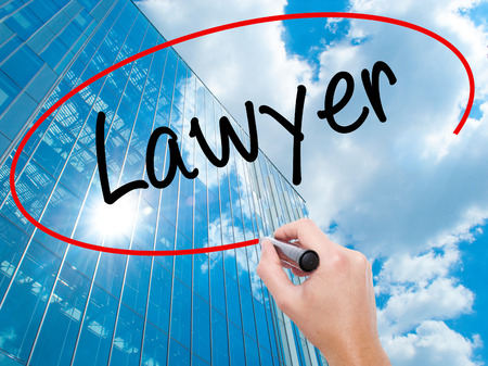 lawer: Man Hand writing Lawyer with black marker on visual screen.  Business, technology, internet concept. Modern business skyscrapers background. Stock Photo