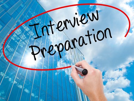 Man Hand writing Interview Preparation with black marker on visual screen. Business, technology, internet concept. Modern business skyscrapers background. Stock Photo