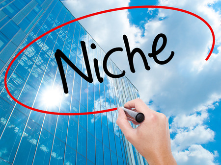 Man Hand writing Niche with black marker on visual screen.  Business, technology, internet concept. Modern business skyscrapers background. Stock Photo Stock Photo
