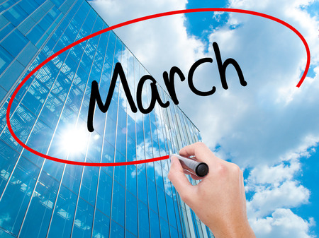 Man Hand writing March with black marker on visual screen. Business, technology, internet concept. Modern business skyscrapers background. Stock Photo
