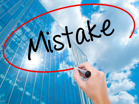 Man Hand writing Mistake with black marker on visual screen.  Business, technology, internet concept. Modern business skyscrapers background. Stock Photo