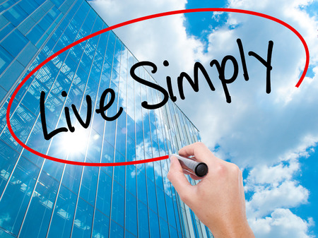 Man Hand writing Live Simply with black marker on visual screen.  Business, technology, internet concept. Modern business skyscrapers background. Stock Photo