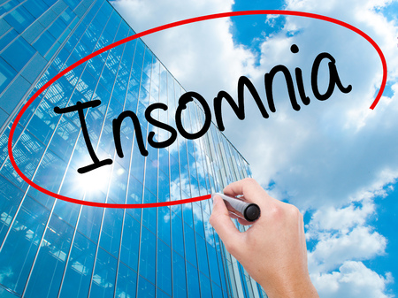 Man Hand writing Insomnia  with black marker on visual screen.  Business, technology, internet concept. Modern business skyscrapers background. Stock Photo Stock Photo