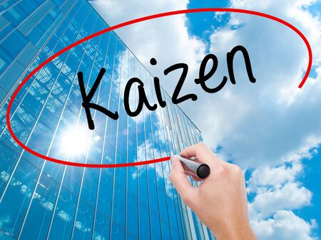 Man Hand writing Kaizen with black marker on visual screen. Business, technology, internet concept. Modern business skyscrapers background. Stock Photo