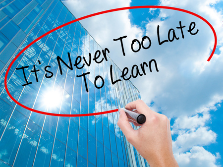 Man Hand writing Its Never Too Late To Learn with black marker on visual screen.  Business, technology, internet concept. Modern business skyscrapers background. Stock Photo Stock Photo