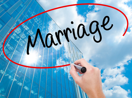 Man Hand writing Marriage with black marker on visual screen. Business, technology, internet concept. Modern business skyscrapers background. Stock Photo Stock Photo
