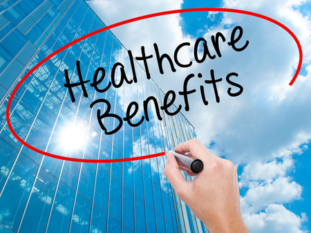 Man Hand writing Healthcare Benefits with black marker on visual screen. Business, technology, internet concept. Modern business skyscrapers background. Stock Photo