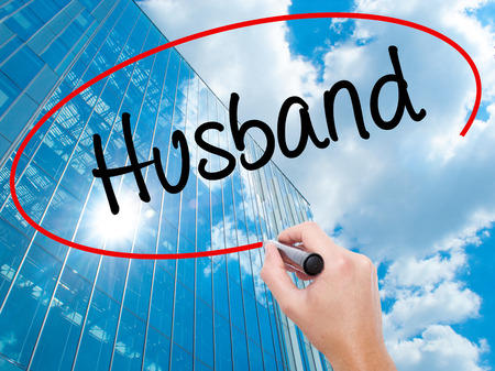 Man Hand writing Husband with black marker on visual screen.  Business, technology, internet concept. Modern business skyscrapers background. Stock Photo