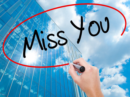 natural love: Man Hand writing Miss You with black marker on visual screen.  Business,  technology, internet concept. Modern business skyscrapers background. Stock Photo Stock Photo