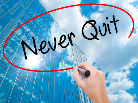 Man Hand writing Never Quit with black marker on visual screen.  Business, technology, internet concept. Stock  Photo