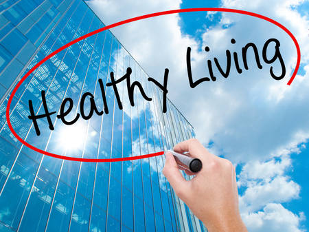 Man Hand writing Healthy Living  with black marker on visual screen. Business, technology, internet concept. Modern business skyscrapers background. Stock Image