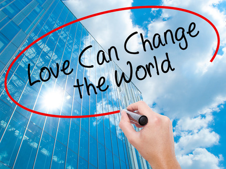 Man Hand writing Love Can Change the World with black marker on visual screen.  Business, technology, internet concept. Modern business skyscrapers background. Stock Photo