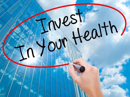 Hombre de la mano escribiendo Invierta en su salud con marcador negro en la pantalla visual. Negocios, la tecnología, el concepto de internet. Fondo moderno de los rascacielos de negocios. Foto de stock