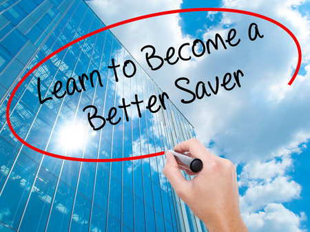 become: Man Hand writing Learn to Become a Better Saver with black marker on visual screen. Business, technology, internet concept. Stock Photo