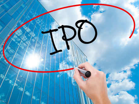 Man Hand writing IPO (Initial Public Offering)   with black marker on visual screen.  Business, technology, internet concept. Modern business skyscrapers background. Stock Photo
