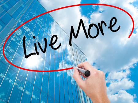 longevity: Man Hand writing Live More with black marker on visual screen.  Business, technology, internet concept. Modern business skyscrapers background. Stock Photo