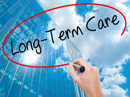 pflegeversicherung: Man Hand writing Long-Term Care with black marker on visual screen. Business, technology, internet concept. Modern business skyscrapers background. Stock Photo