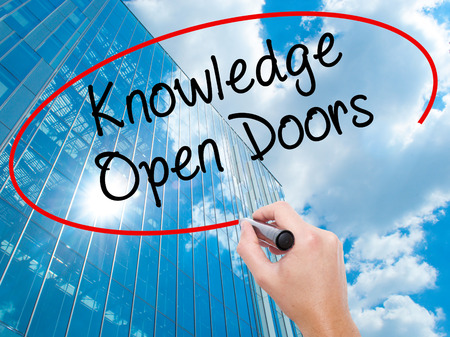 Man Hand writing  Knowledge Open Doors  with black marker on visual screen.  Business, technology, internet concept. Modern business skyscrapers background. Stock Photo