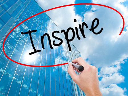 Man Hand writing Inspire  with black marker on visual screen.  Business, technology, internet concept. Modern business skyscrapers background. Stock Photo