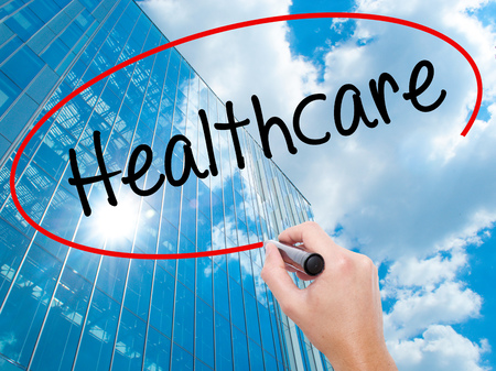 Man Hand writing Healthcare with black marker on visual screen. Business, technology, internet concept. Modern business skyscrapers background. Stock Photo