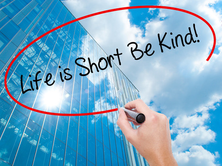 Man Hand writing Life is Short Be Kind! with black marker on visual screen. Business, technology, internet concept. Modern business skyscrapers background. Stock Photo