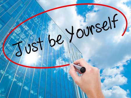esteemed: Man Hand writing Just be Yourself with black marker on visual screen.  Business, technology, internet concept. Modern business skyscrapers background. Stock Photo Stock Photo