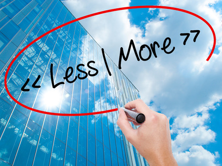 Man Hand writing Less - More with black marker on visual screen.  Business, technology, internet concept. Modern business skyscrapers background. Stock Photo Stock Photo