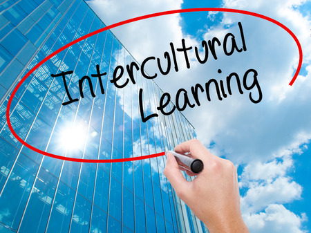 intercultural: Man Hand writing Intercultural Learning with black marker on visual screen. Business, technology, internet concept. Modern business skyscrapers background. Stock Photo