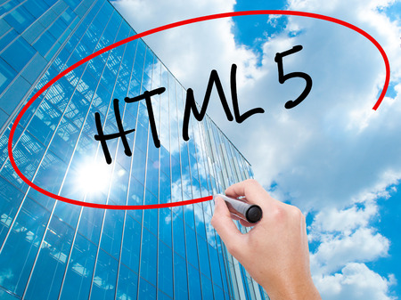 Man Hand writing HTML 5 with black marker on visual screen. Business, technology, internet concept. Modern business skyscrapers background. Stock Photo