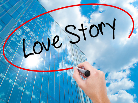Man Hand writing Love Story with black marker on visual screen. Business, technology, internet concept. Modern business skyscrapers background. Stock Photo