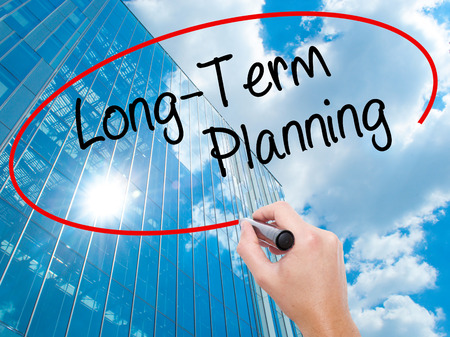 Man Hand writing  Long-Term Planning with black marker on visual screen.  Business, technology, internet concept. Modern business skyscrapers background. Stock Photo Stock Photo